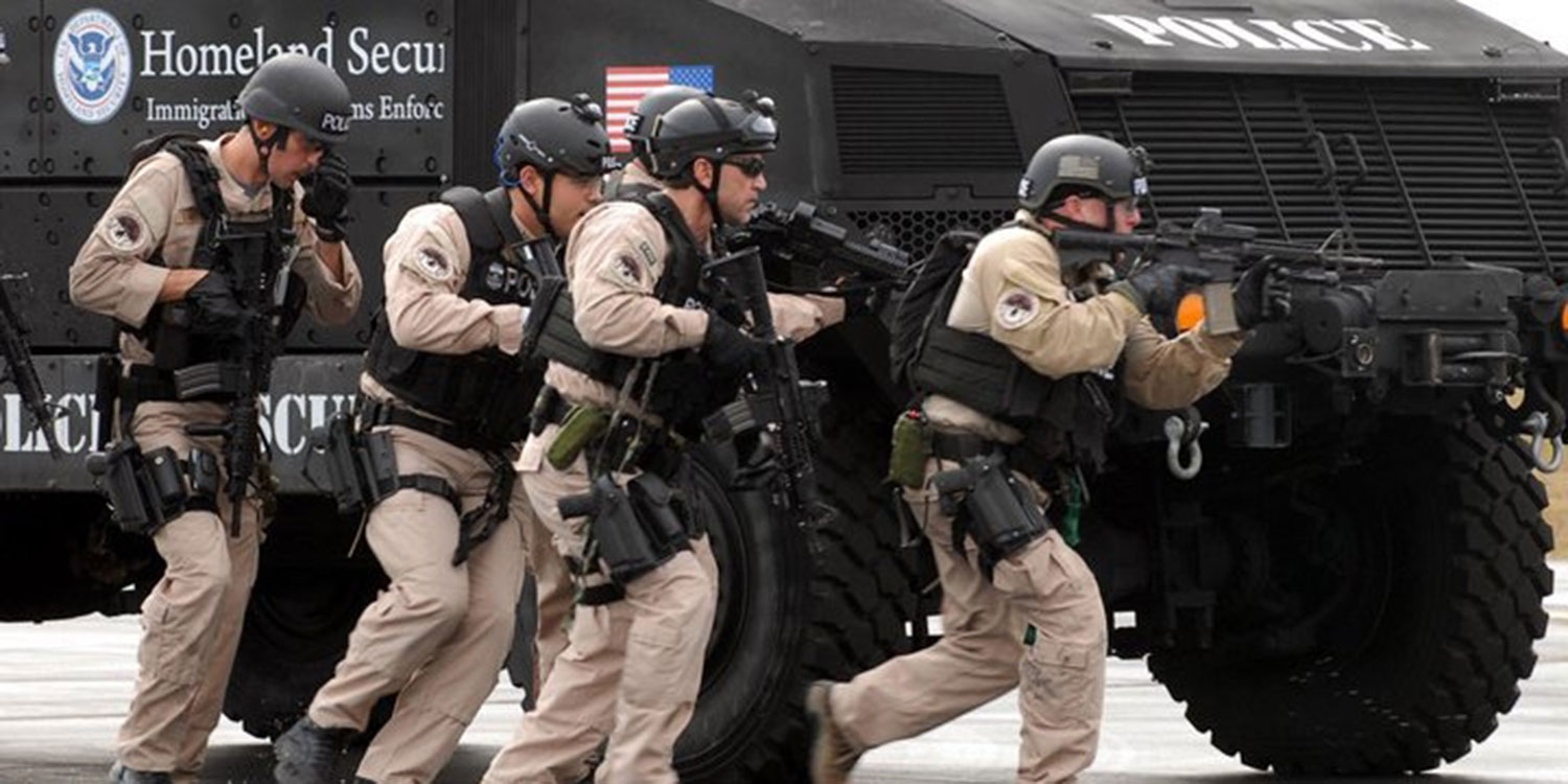 Photo of ICE officers with guns and military vehicles