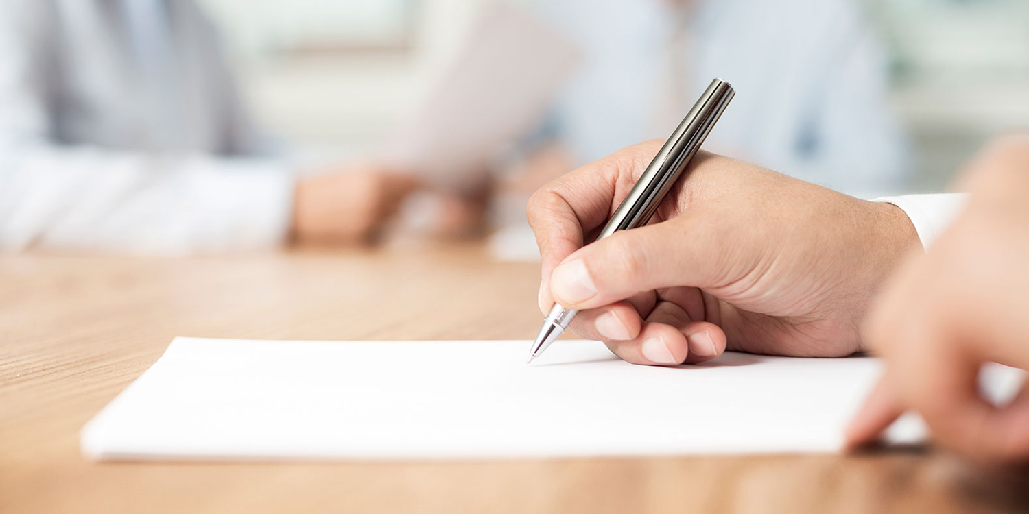 Photo of a hand holding a pen to write