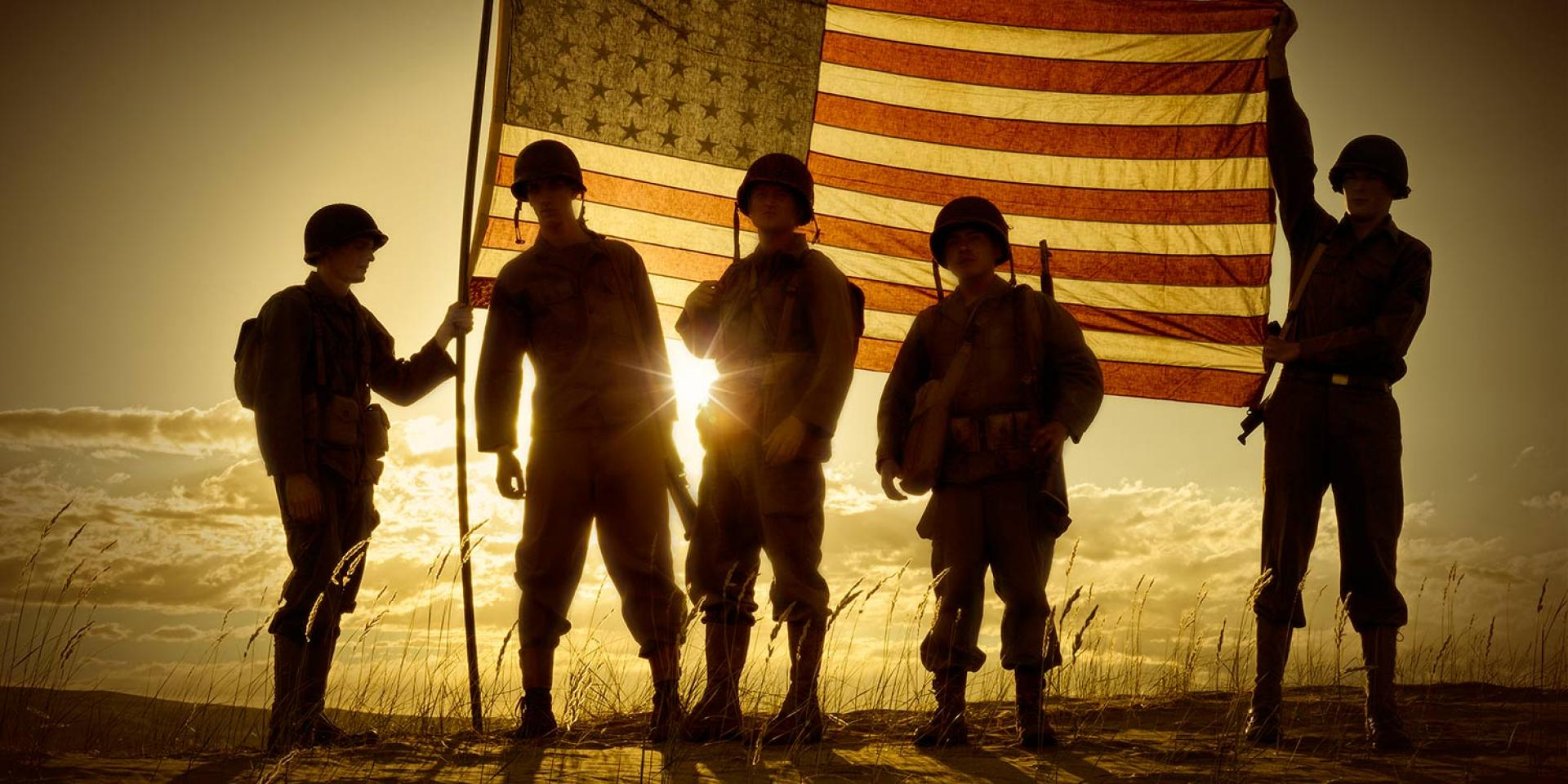 Photo of American soldiers holding up flag and silhouetted by the sun in the background